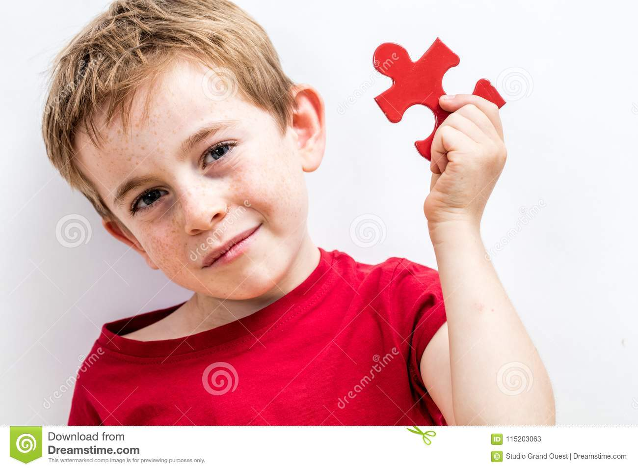 Smiling beautiful boy with freckles finding jigsaw for unique solution