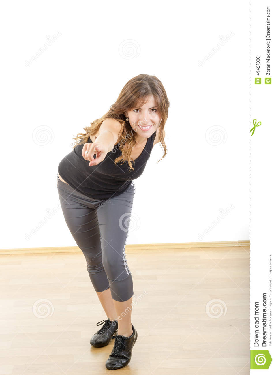 Smiling beautiful sporty fit athletic girl or woman pointing fin