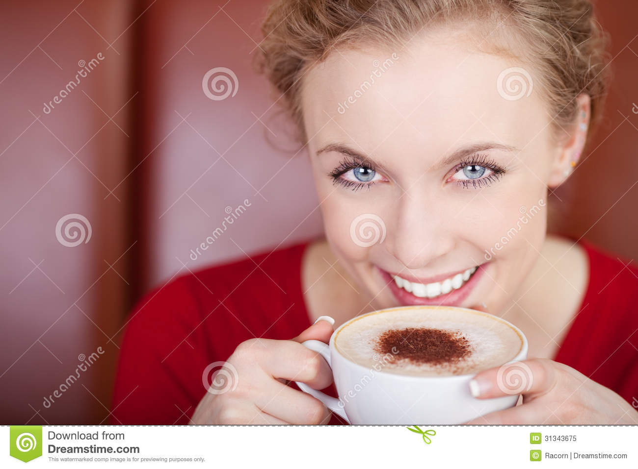 Smiling, beautiful woman drinking cappuccino