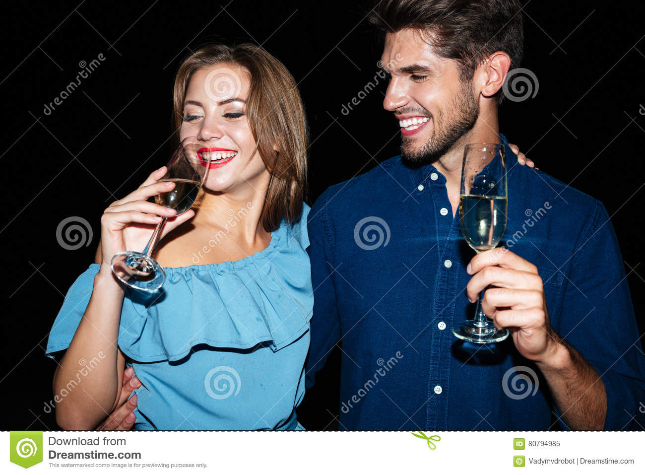 Smiling beautiful young couple drinking champagne at night together