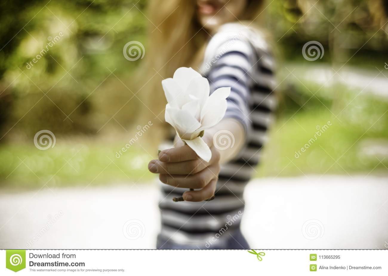Smiling beautiful young woman with a spring flower on sunny warm