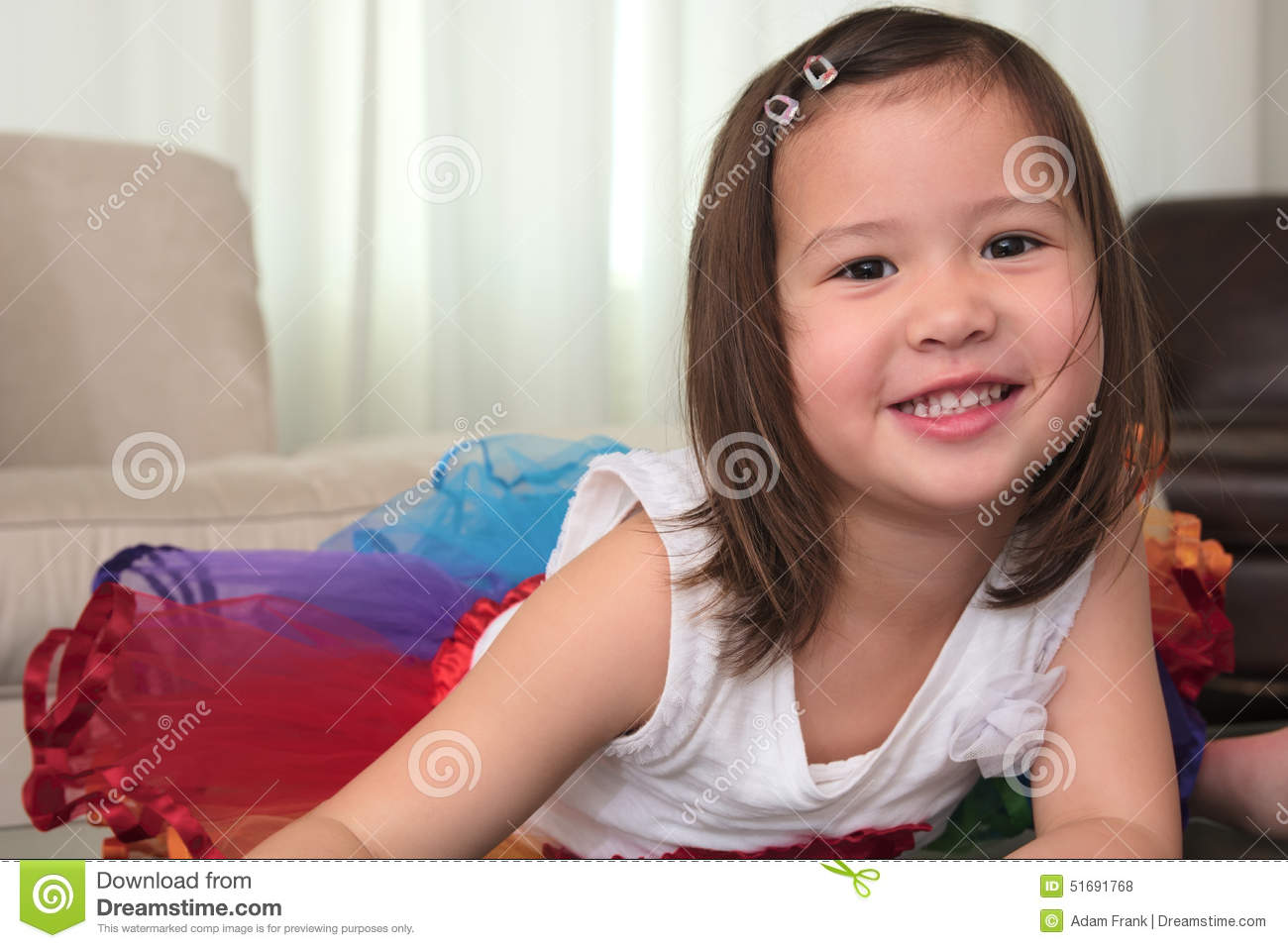 Smiling Biracial Female Asian Child Lying On Stomach