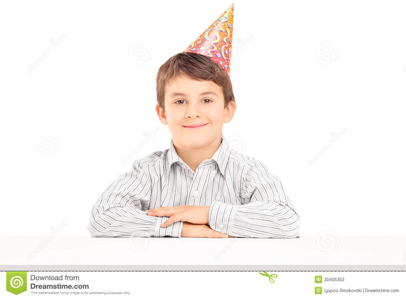 A Smiling Birthday Boy With Party Hat Posing On Table