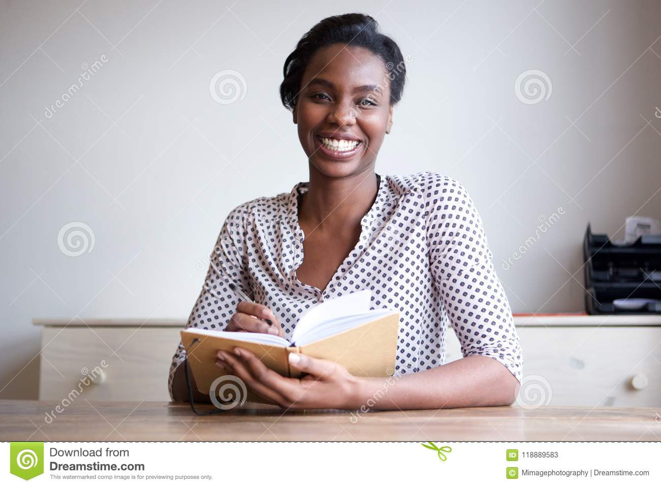 smiling black woman at home writing in journal stock image - image