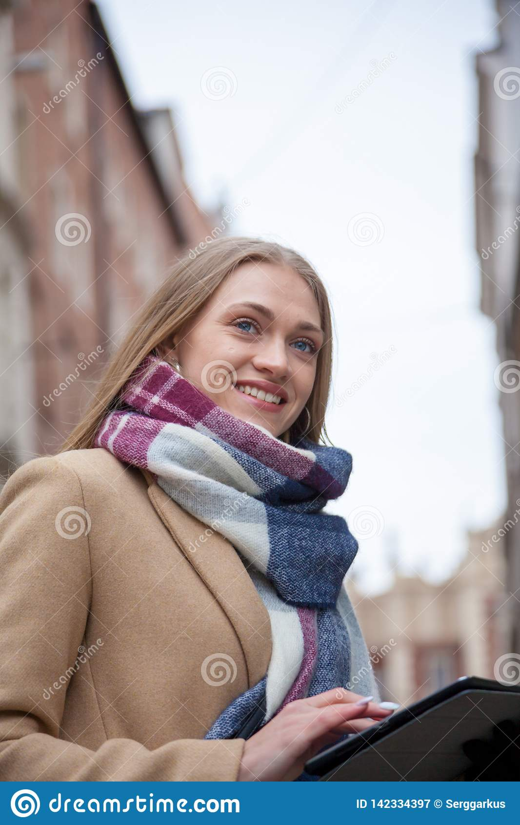 Smiling blonde beautiful woman holding tablet on city street.