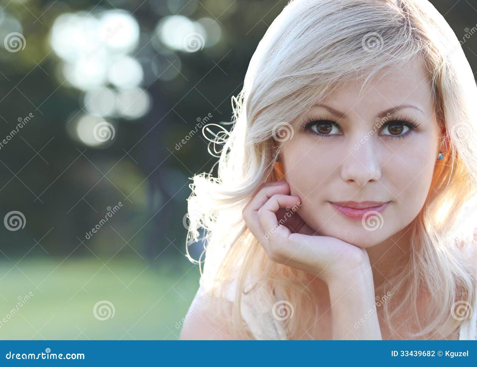Smiling blonde girl. Portrait of happy beautiful young woman, outdoors. Bokeh
