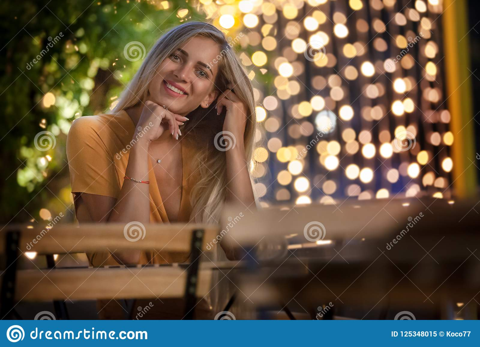 Smiling blonde young woman sitting, with evening fairy lights on the background.