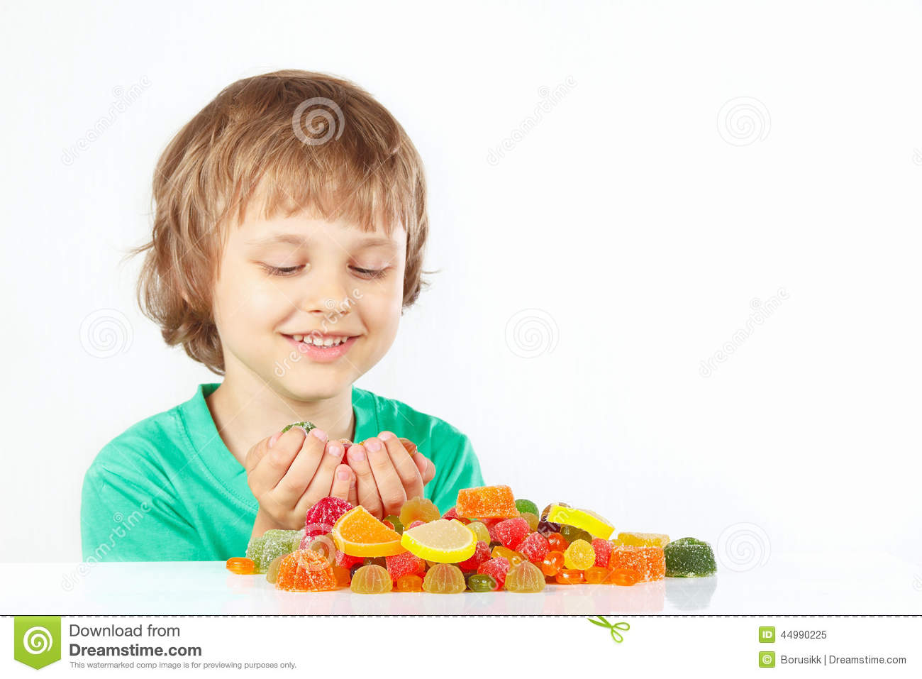 Smiling boy with colored sweets and jelly candies on white background
