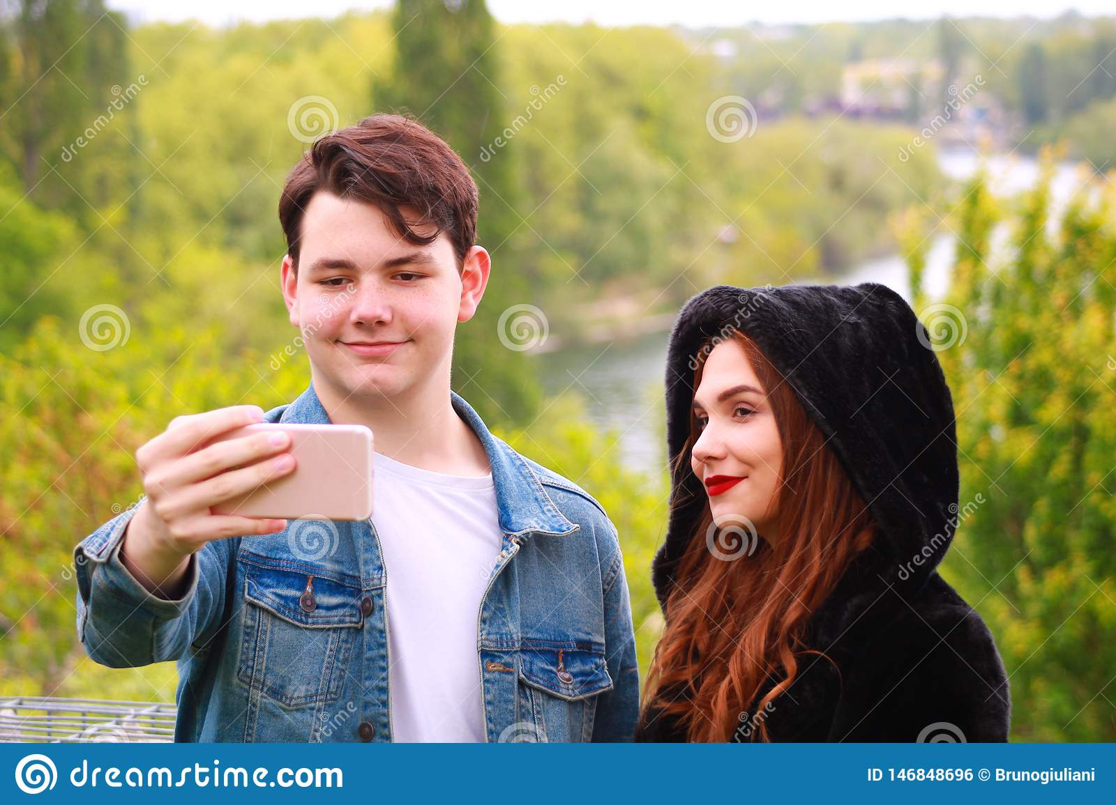 A smiling boy and girl make a selfie in nature. Woman with long red hair