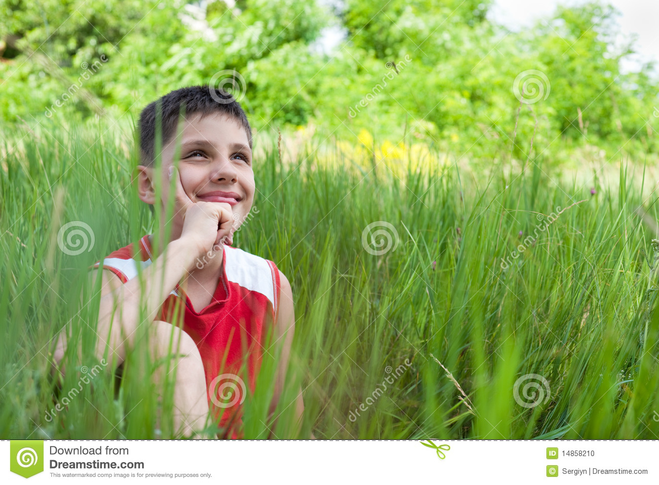 Smiling boy in the green grass