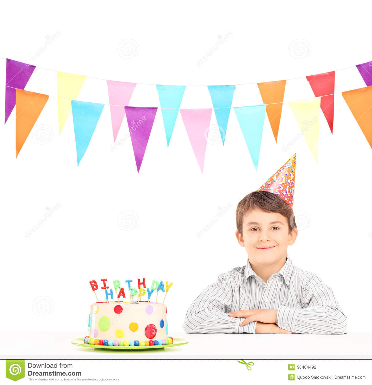 smiling boy with party hat and a birthday cake stock