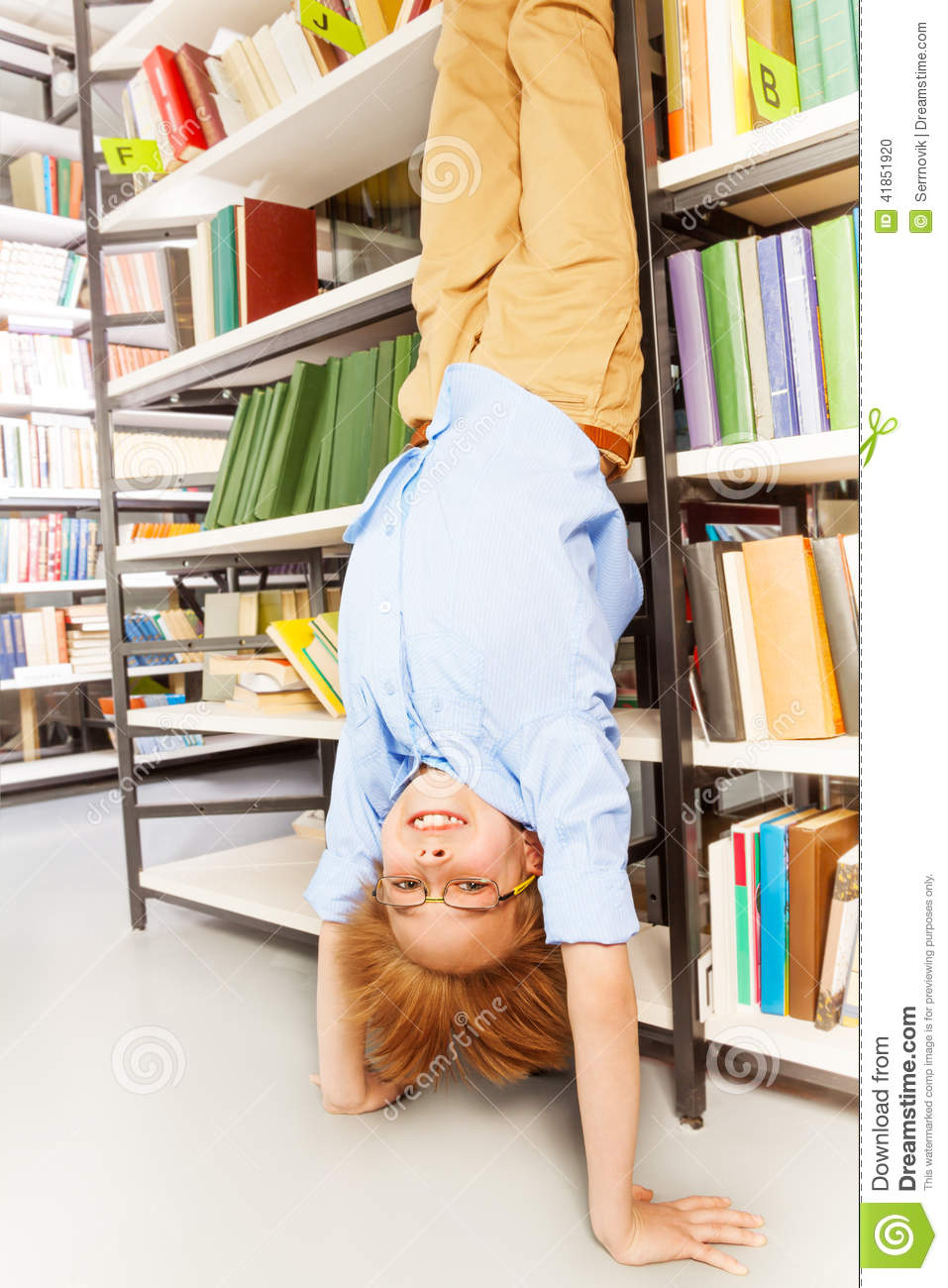 Smiling Boy Standing On Arms Upside Down Stock Photo