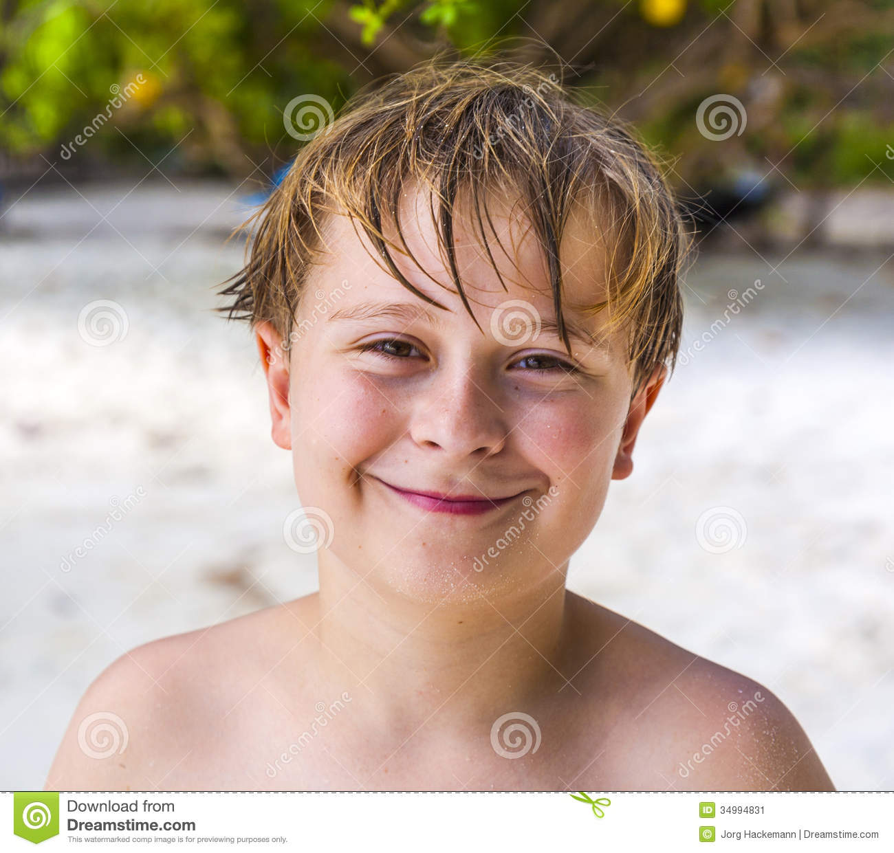 Young Happy Boy With Brown Wet Hair Is Smiling And: Smiling Boy With Wet Hair At The Beach Stock Image