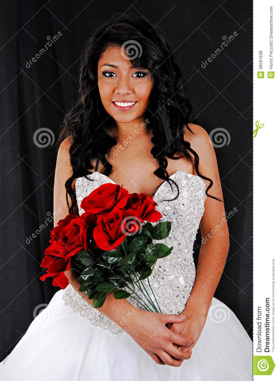 Wedding dress standing forblack background holding a bunch of red