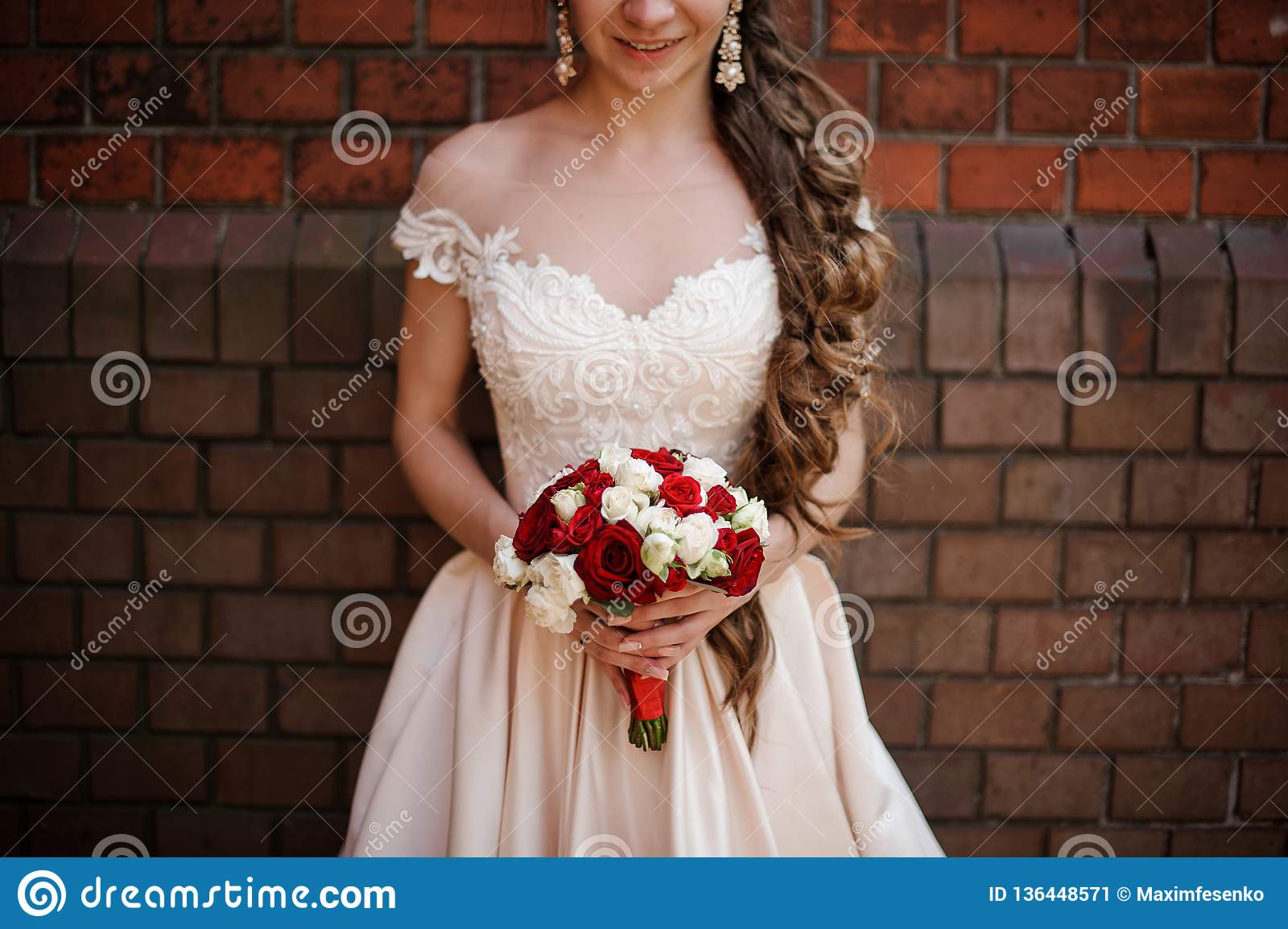 Smiling Bride In White Wedding Dress With A Bouquet Of Red And