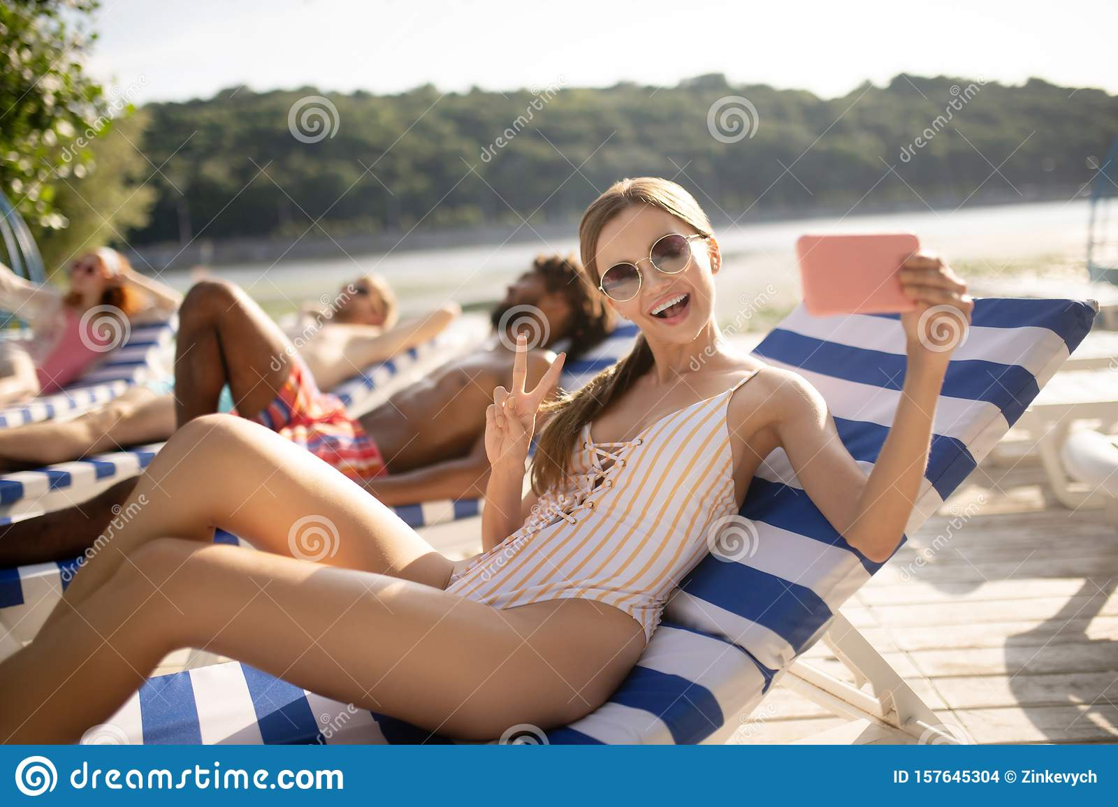 Woman wearing sunglasses smiling broadly making selfie