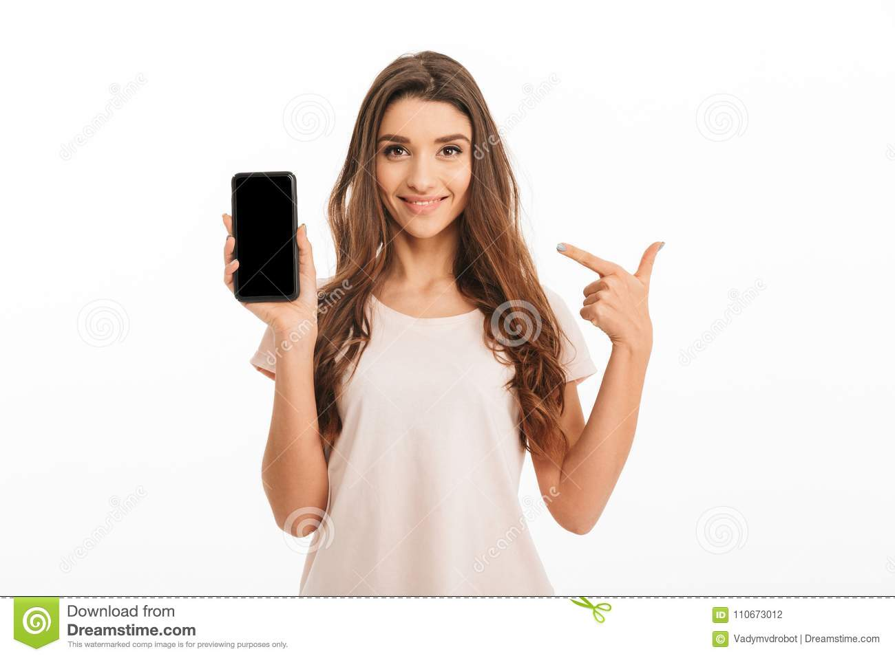 9861da826fbab Smiling brunette woman in t-shirt showing blank smartphone screen and  pointing on it while looking at the camera over grey background