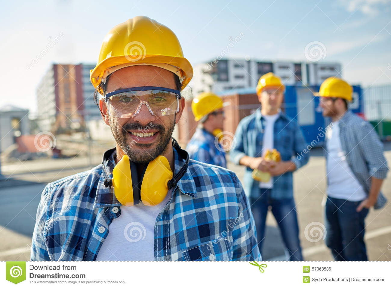 Smiling builder with hardhat and headphones stock photo for Production builder