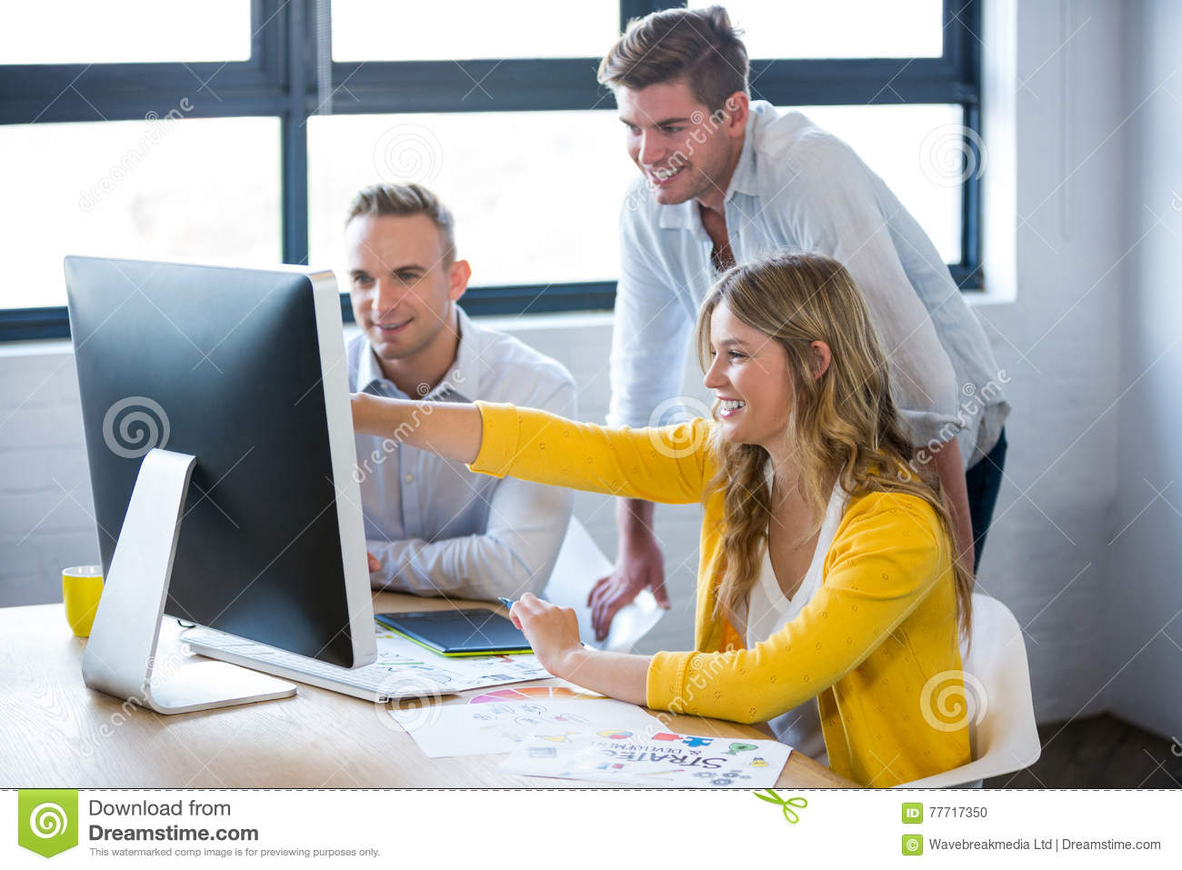 Smiling business people discussing over computer