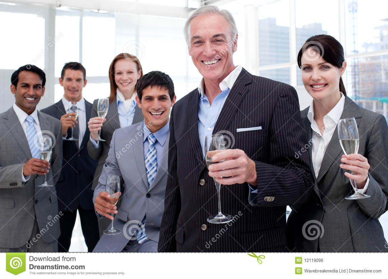 Smiling business team holding glasses of Chamoagne