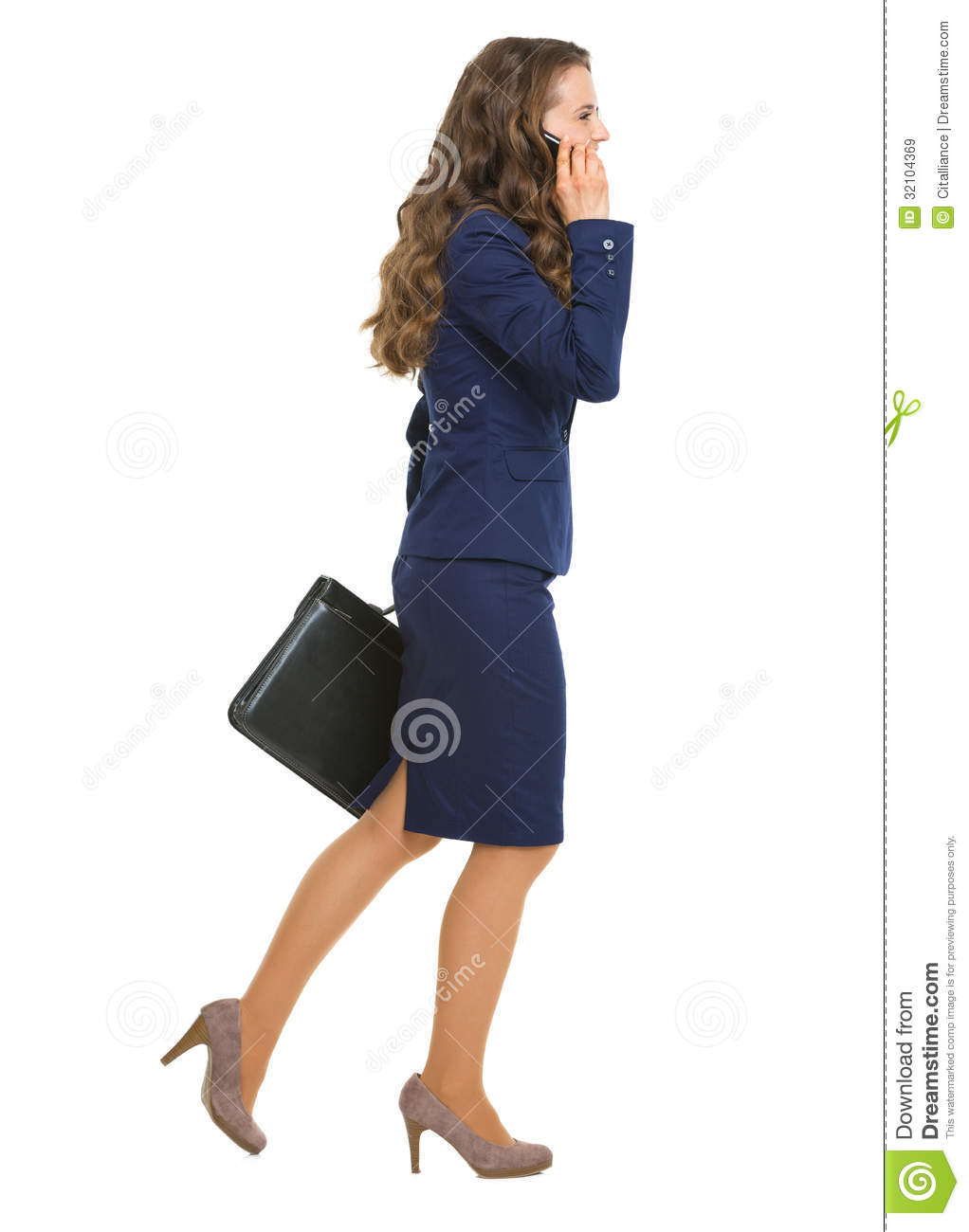 Smiling business woman going sideways talking cell phone