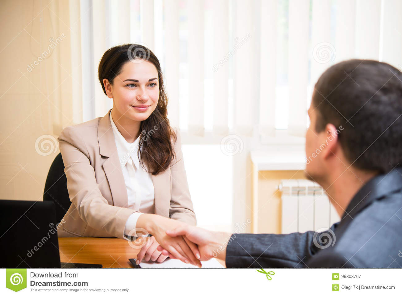 Smiling business woman shakes her hand at the interview