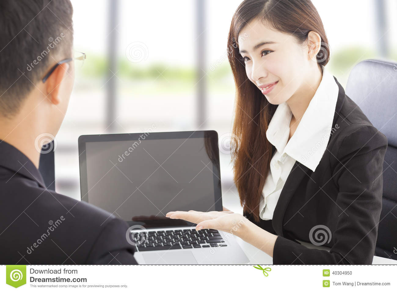 Smiling Business woman showing at laptop and explaining a plan