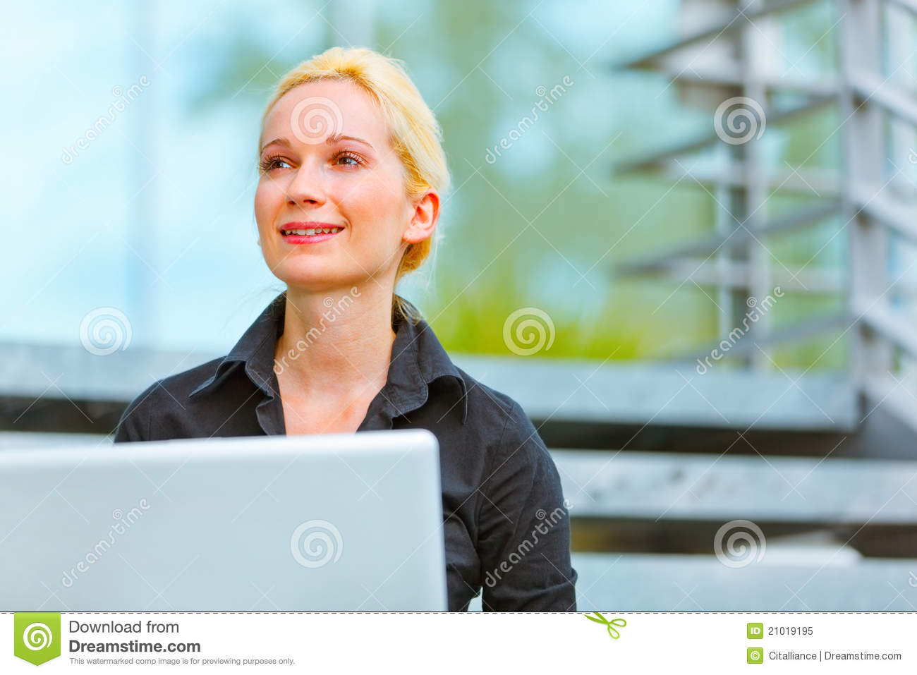 Smiling business woman sitting on stairs at office