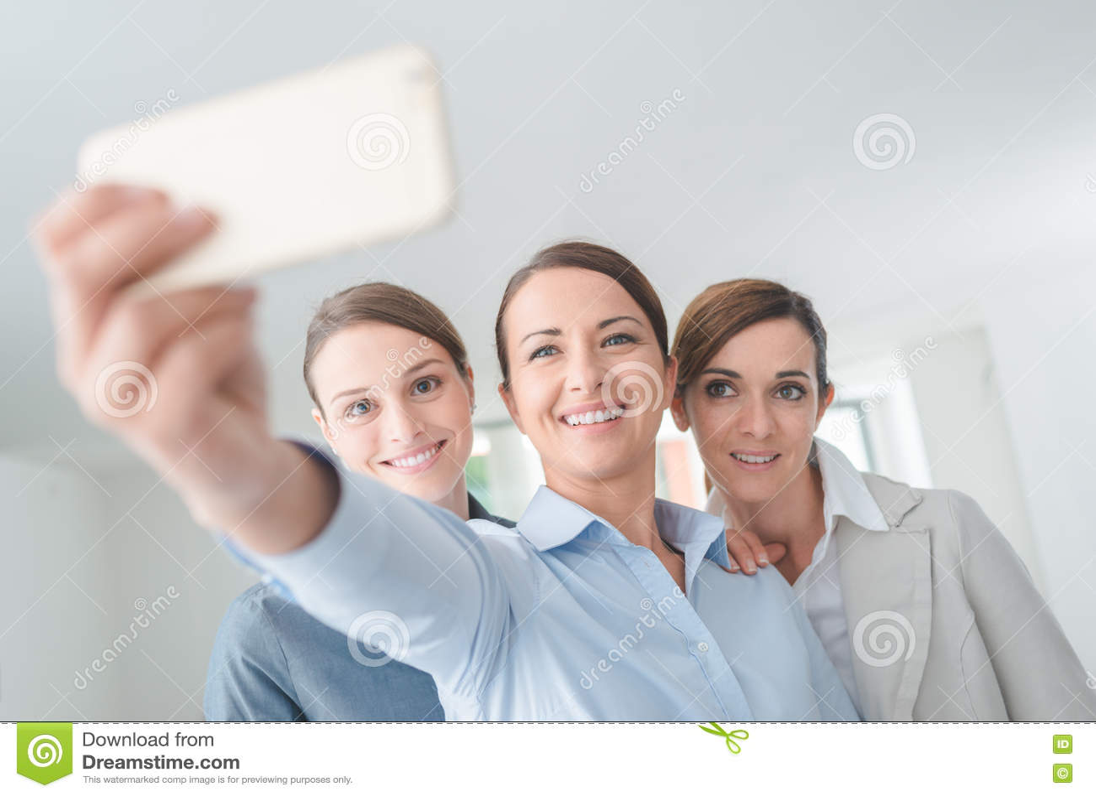 Smiling business women team taking a selfie