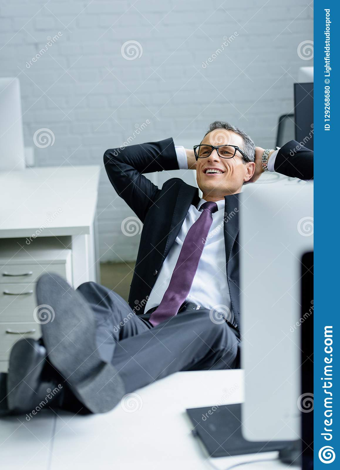 smiling businessman with hands behind head resting