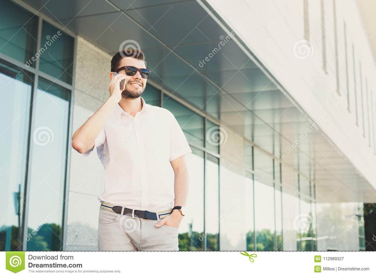 Smiling businessman making a phone call outdoors