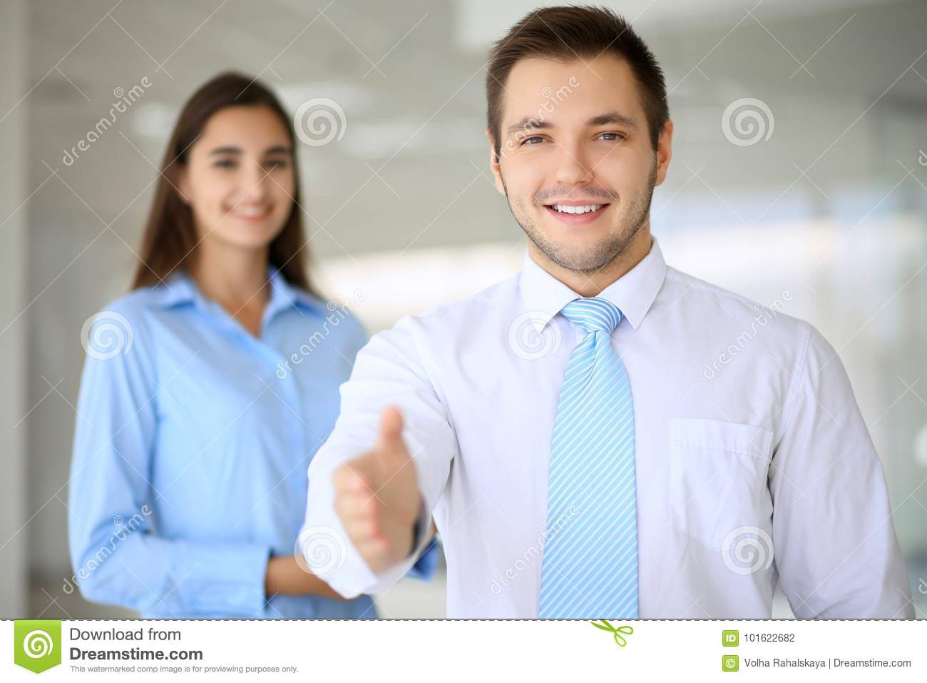 Smiling businessman in office is ready for shaking hands