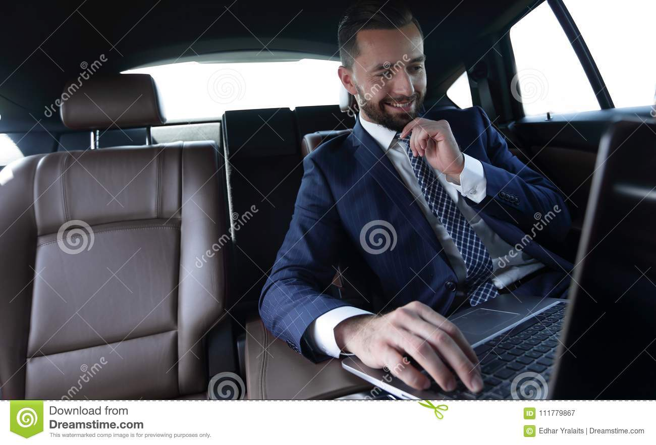 Businessman reads information on laptop while sitting in car
