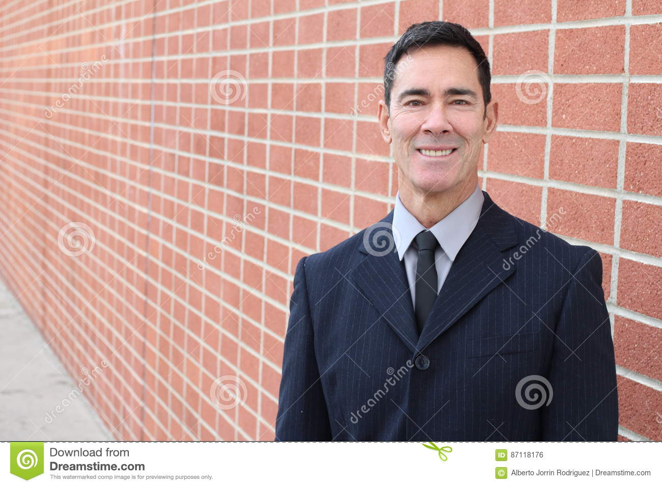Smiling businessman on urban brick wall background with copy space