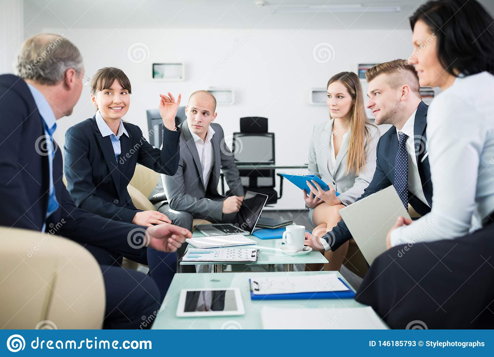 Smiling Businesswoman Discussing With Colleagues In Office