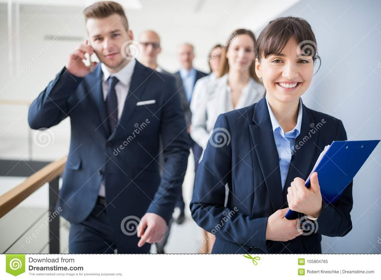 Smiling Businesswoman Holding Clipboard While Walking With Team