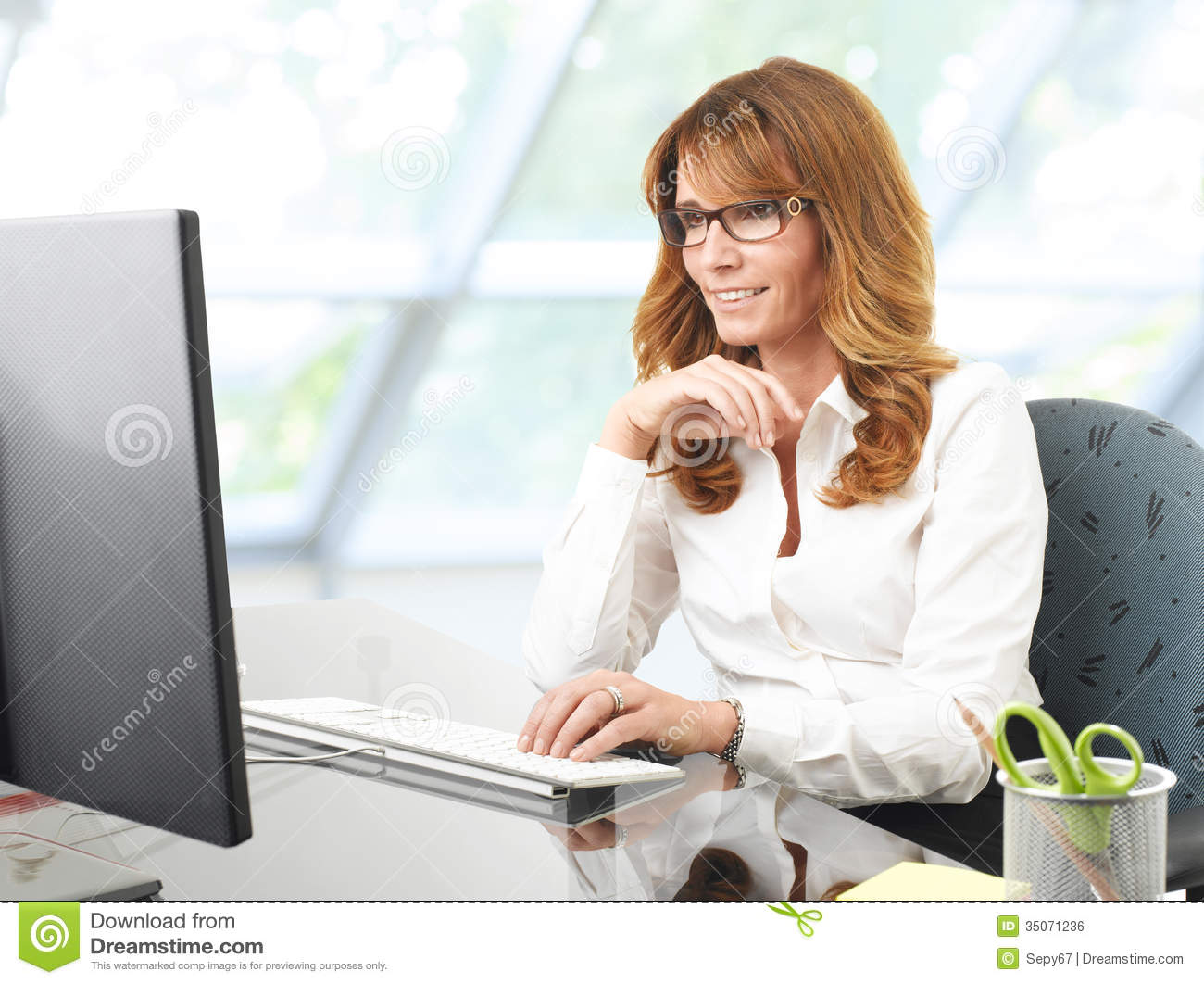 Free Stock Image: Smiling businesswoman at office desk with a computer