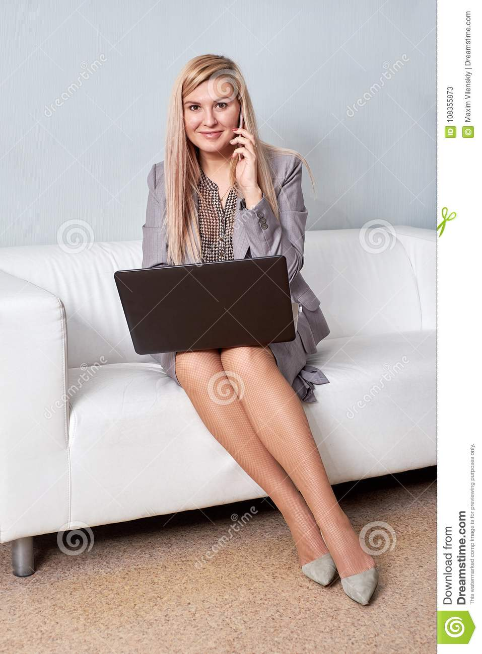 Smiling businesswoman sitting on sofa with laptop computer in office lobby