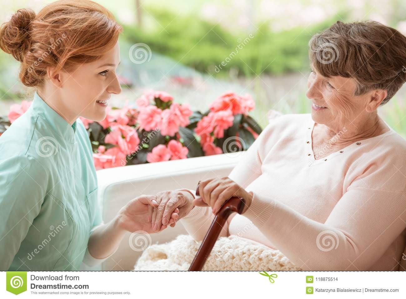 Smiling caregiver supporting happy senior woman with walking sti