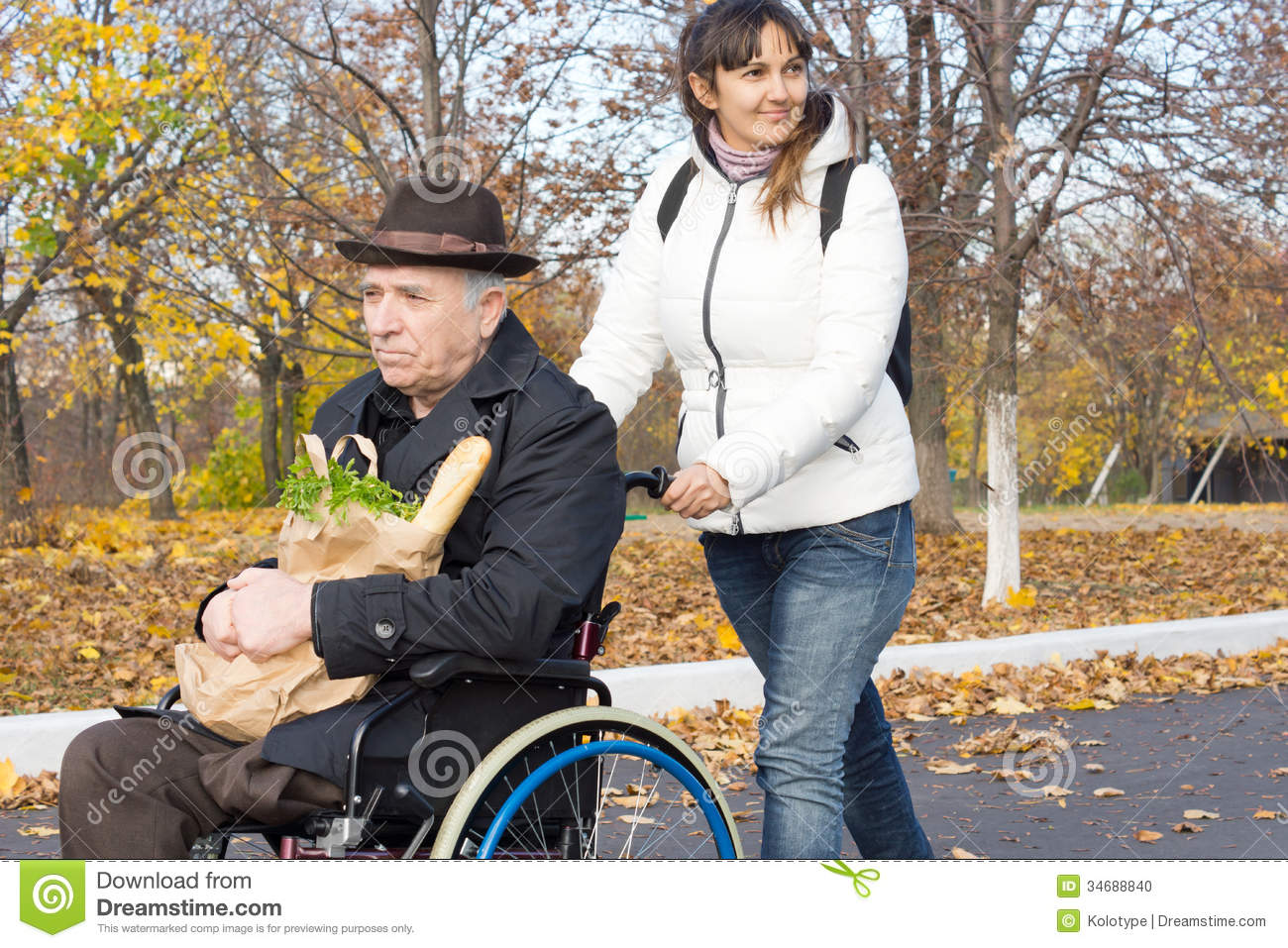 Smiling Carer Pushing An Old Man In A Wheelchair Stock