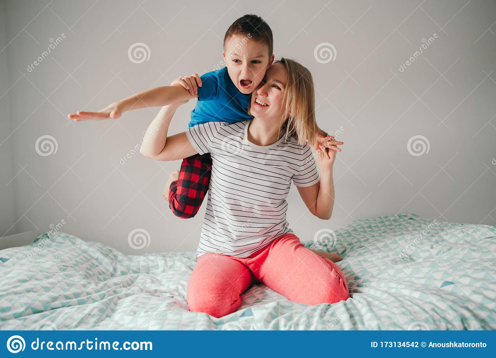 Smiling Caucasian Mother And Boy Son Playing In Bedroom At Home
