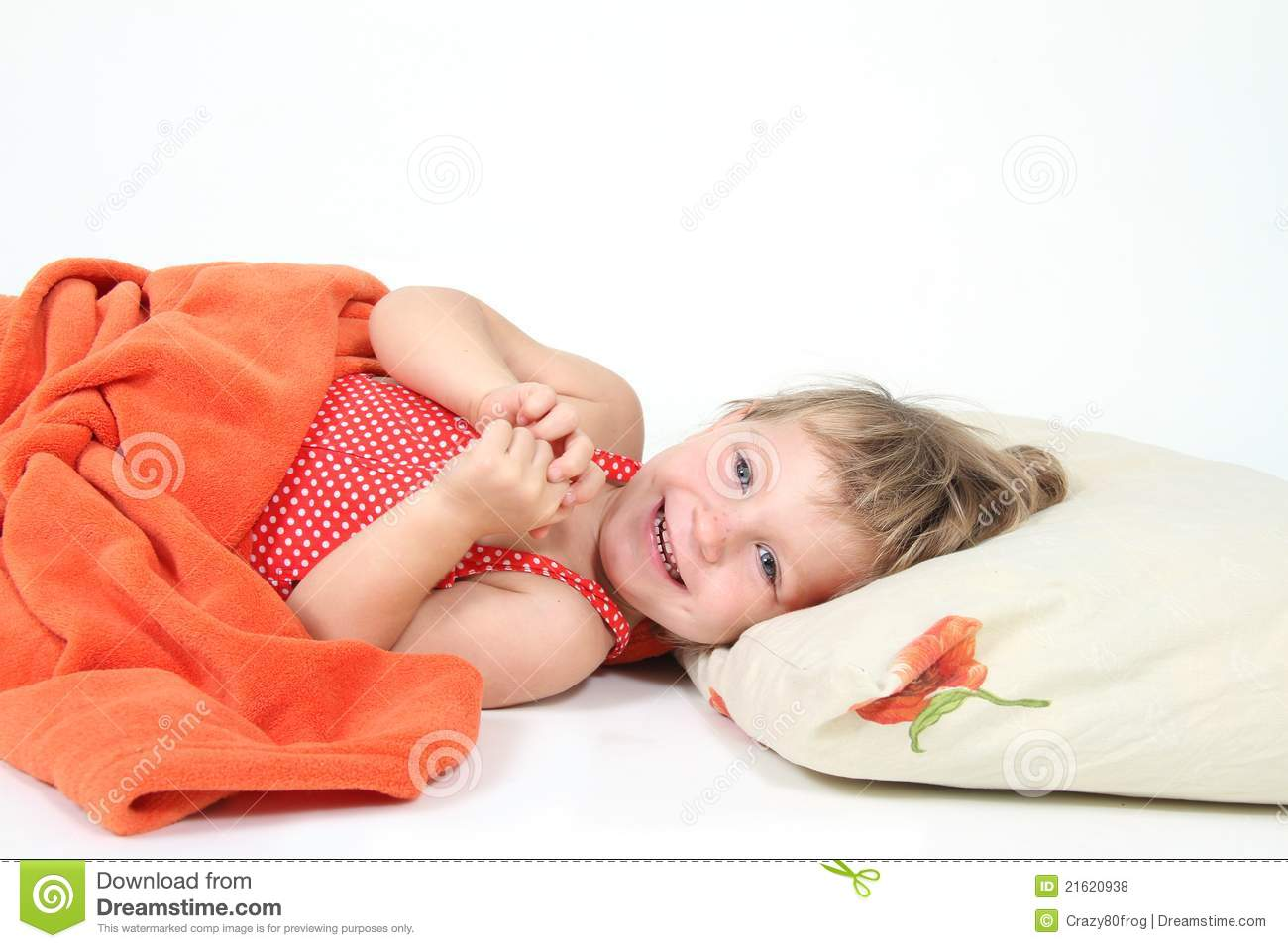 Smiling child in bed over white