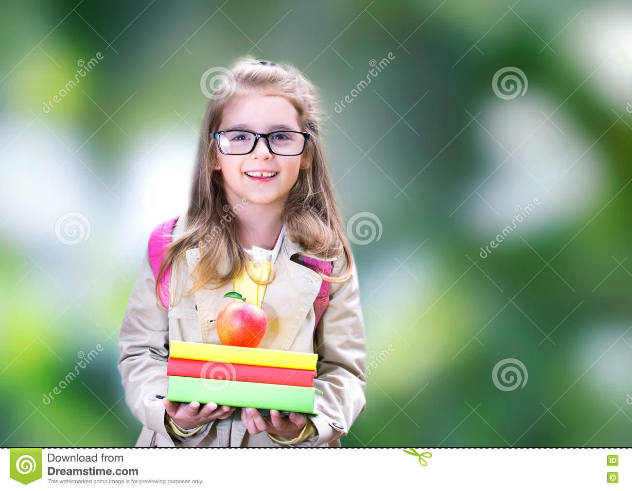 Smiling child girl with books backpack apple. Back to school.