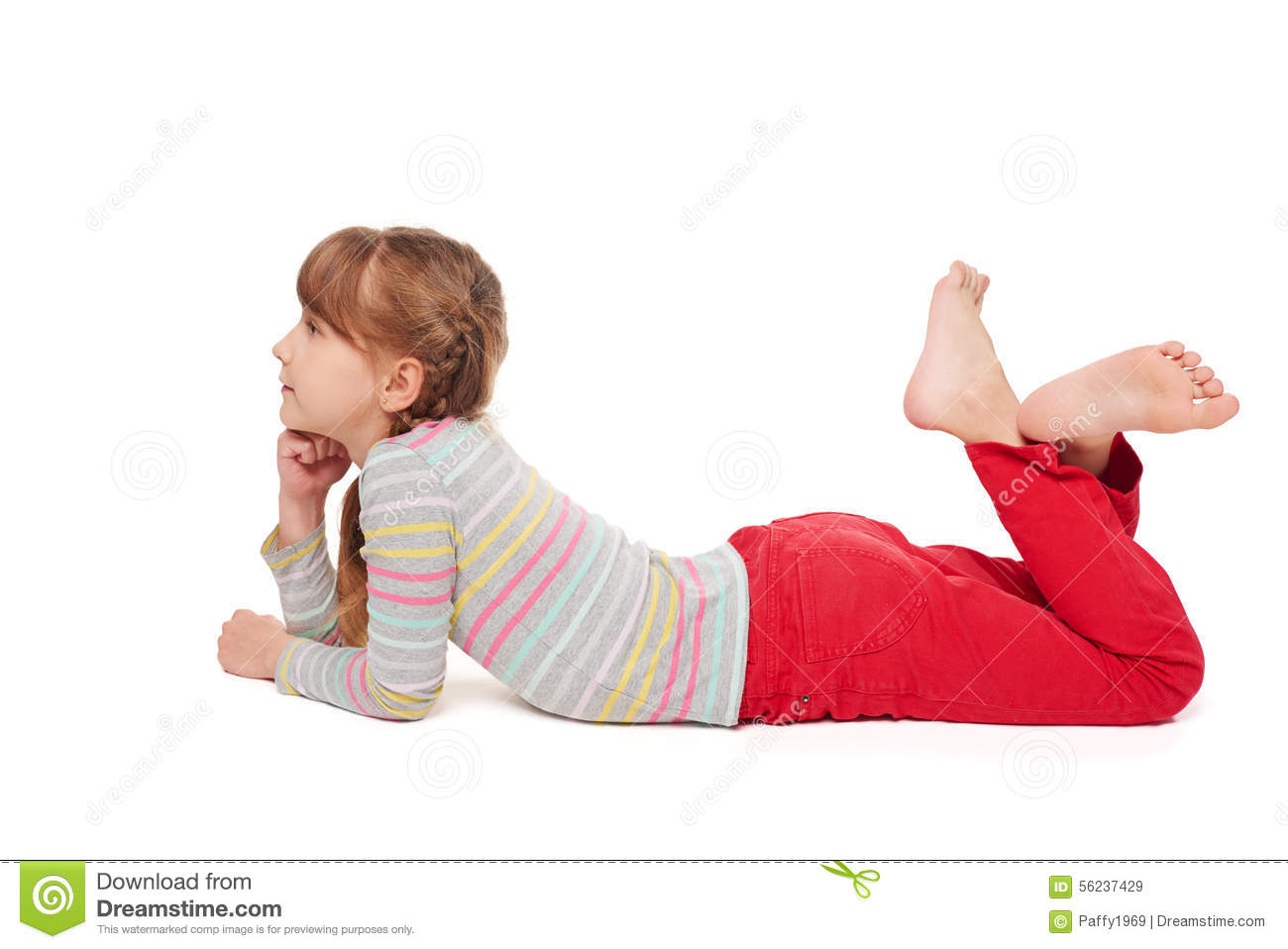 Preteen girl lying on stomach using laptop computer Stock
