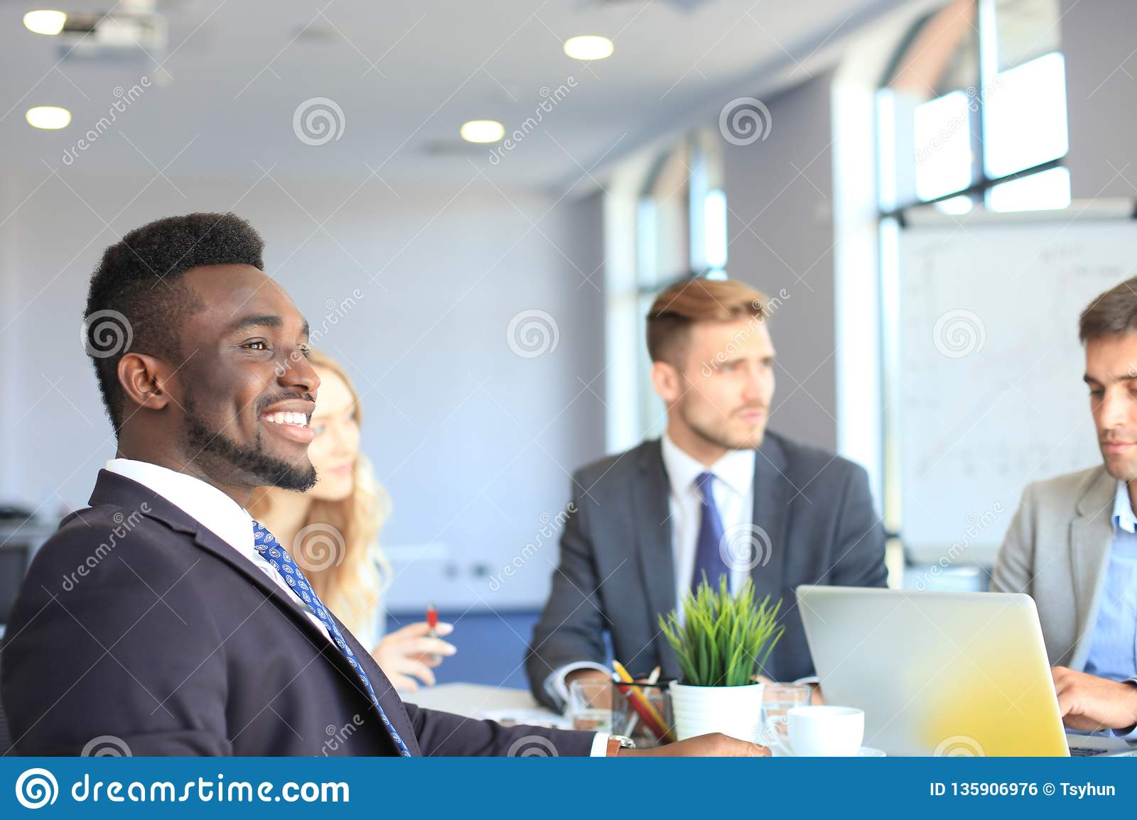 Smiling confident African businessman in a meeting with a colleagues seated at a conference table in the office.