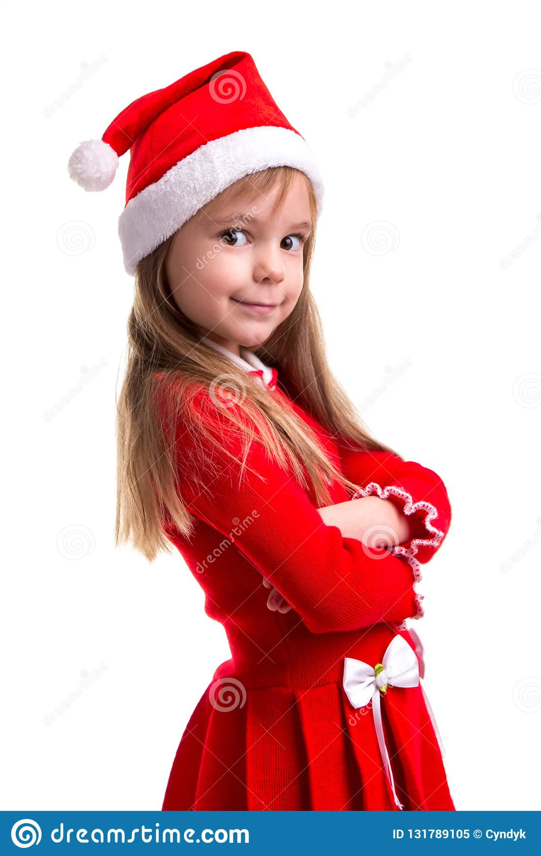 Smiling coquettish christmas girl wearing a santa hat isolated over a white background, standing in the half turn