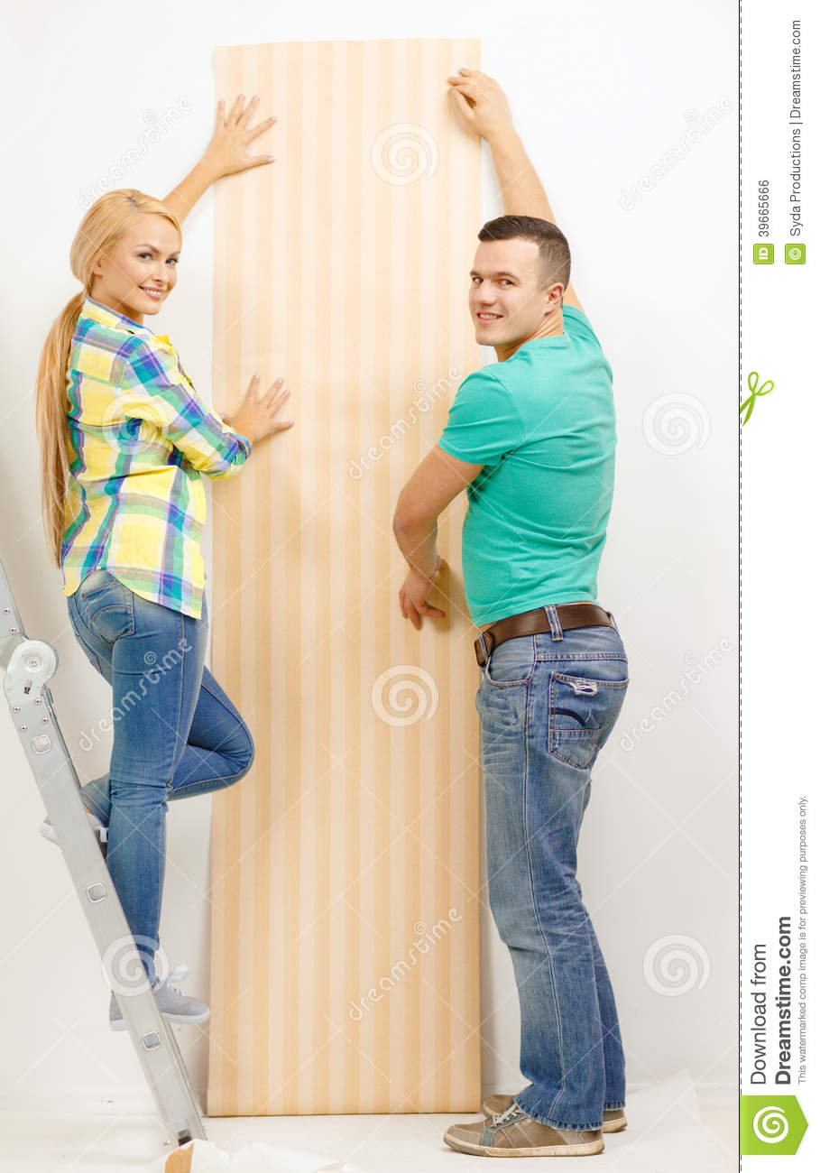 Smiling couple choosing wallpaper for new home stock photo for Wallpaper new home