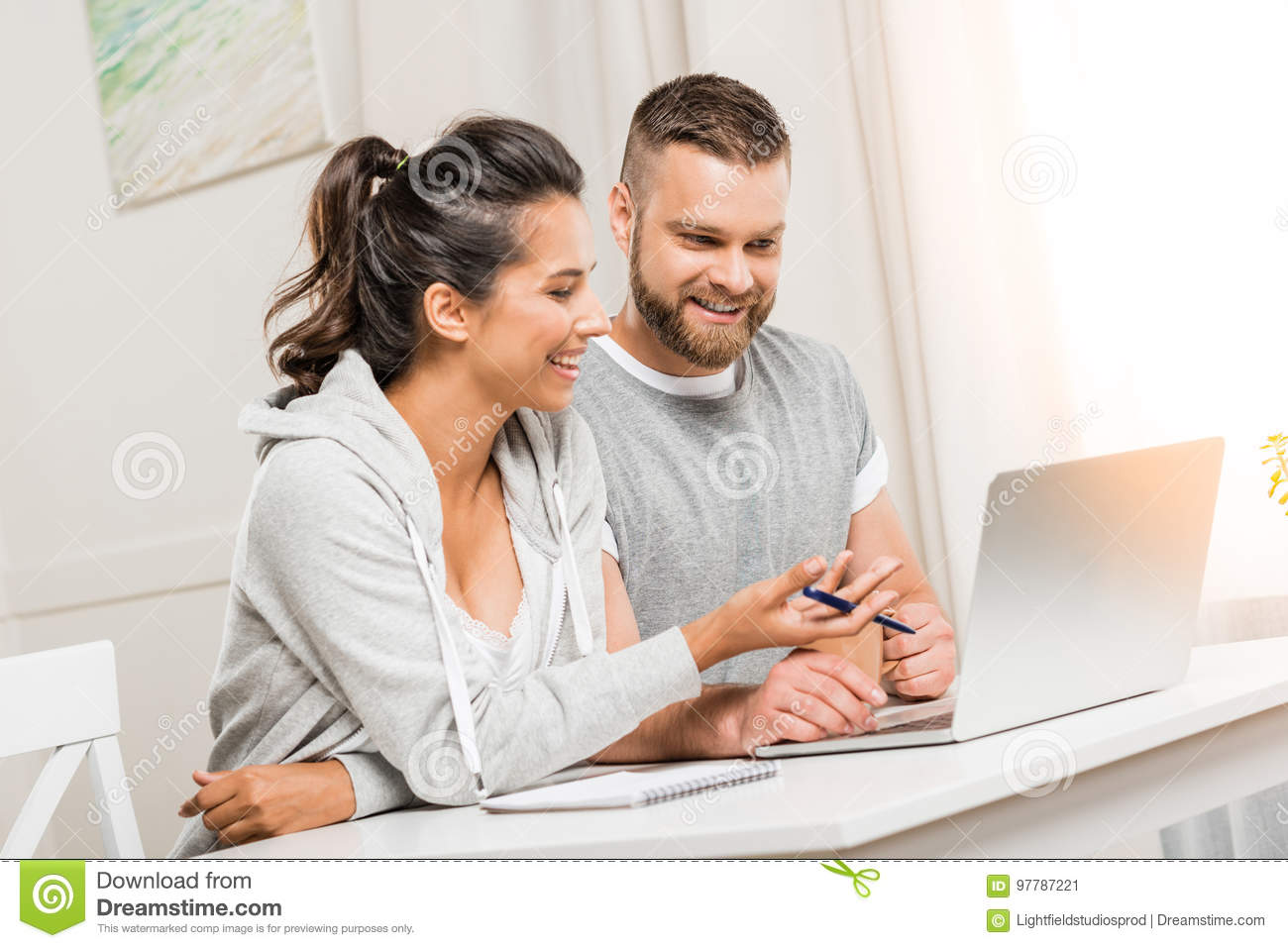 Smiling couple discussing project while working at home together