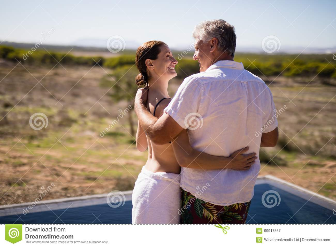 Smiling couple embracing near poolside