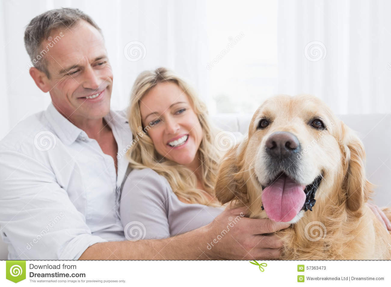 Smiling Couple Petting Their Golden Retriever On The Couch Stock